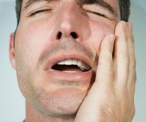 Man holding his cheek, eyes closed, close-up
